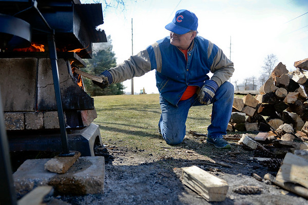 BEN MIKESELL | THE GOSHEN NEWS<br /> Glenn Stutzman adds wood to the fire heating his batch of maple syrup in his backyard on Apple Lane in Goshen. Stutzman said he has to add more wood every 30 minutes to keep the syrup boiling.