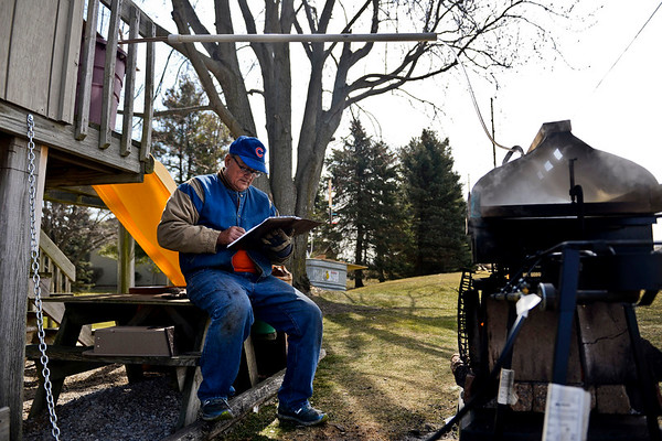 BEN MIKESELL | THE GOSHEN NEWS<br /> Glenn Stutzman sifts through his ledger while he tends to his batch of maple syrup boiling Monday in his backyard on Apple Lane in Goshen. In his second year making syrup, Stutzman rigged up his playground to store sap and drip it into the vat below.