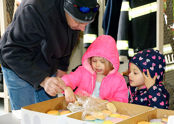 JOHN KLINE | THE GOSHEN NEWS<br /> Nappanee resident Phil Steele, left, helps Hadley Abney, 5, center, and Abigail Abney, 3, right, both of Shipshewana, pick out a complementary cookie following the annual Middlebury Township Fire Department Easter Egg Hunt Saturday in downtown Middlebury.