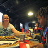 GEOFF LESAR | THE GOSHEN NEWS<br /> <br /> Patty Burns, a founding member of the Goshen Clay Artists Guild, serves dessert to Tyshawn Eubanks, 8, of Elkhart, during the 18th annual Empty Bowl Soup Supper in Goshen.