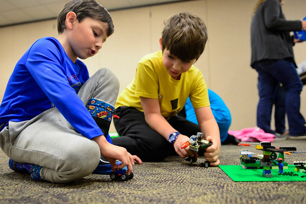 "BEN MIKESELL | THE GOSHEN NEWS<br /> Six-year-old Lucas Garcia of Middlebury, left, plays with Ethan Graber, 9, during LEGO Club Tuesday at Middlebury Community Public Library. The monthly gathering lets children from five to fifth grade mingle and play with LEGOS donated to the library. ""My favorite LEGOs are Batman and Superman,"" Garcia said as he drove his LEGO vehicle around the floor."