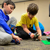 """BEN MIKESELL   THE GOSHEN NEWS<br /> Six-year-old Lucas Garcia of Middlebury, left, plays with Ethan Graber, 9, during LEGO Club Tuesday at Middlebury Community Public Library. The monthly gathering lets children from five to fifth grade mingle and play with LEGOS donated to the library. """"My favorite LEGOs are Batman and Superman,"""" Garcia said as he drove his LEGO vehicle around the floor."""