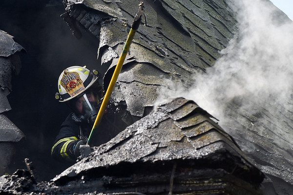 BEN MIKESELL | THE GOSHEN NEWS<br /> North Webster Fire Department battalion chief Kenny Gunkel uses a pike pole to chip away at the roof while responding to a house fire Wednesday morning at 10469 N Syracuse-Webster Road in Syracuse. Syracuse Fire Department responded to the fire about 9 a.m. and called North Webster and Milford Fire Departments for additional help.