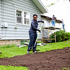 LEANDRA BEABOUT | THE GOSHEN NEWS<br /> Goshen resident Simelwa Dlova helps spread soil to even out the yard of a house on Denver Ave. as part of LaCasa's annual Help a House day.