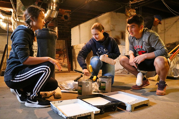 LEANDRA BEABOUT | THE GOSHEN NEWS<br /> From left: Maija Short, Alisha Snyder and Isaac Sawatzky prepare to paint a basement on Denver Ave. as a part of LaCasa's annual Help a House day.