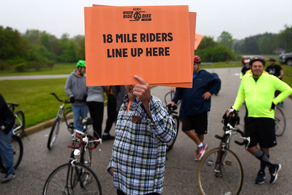 BEN MIKESELL | THE GOSHEN NEWS<br /> Tommy Hondorp, Granger, holds up a sign to organize the bikers into groups before ADEC's Ride-A-Bike fundraiser Saturday morning at Northridge High School in Middlebury.