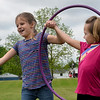 BEN MIKESELL | THE GOSHEN NEWS<br /> First-grade students Madilyn Thwaits, left, and Cora Snavely, right, work to move a hula hoop without unlinking hands during Field Day Tuesday at Benton Elementary School.