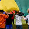 BEN MIKESELL | THE GOSHEN NEWS<br /> Kindergarten students in Jacinda Metz's class hold onto a playground parachute during Field Day Tuesday at Benton Elementary School. Students took turns running underneath while others held it up.