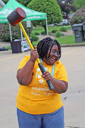 Roger Schneider | The Goshen News<br /> Kieress Baker of Goshen takes a break from selling lemonade at the Goshen Lemonpalooza, to try her hand at the bell-ringing game. The Goshen site featured games for children, a Latino food truck and two remote radio station broadcasts.