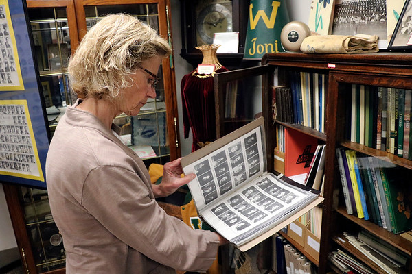 GEOFF LESAR | THE GOSHEN NEWS<br /> <br /> Syracuse-Wawasee Historical Museum Board Member Mary Hursch flips through photos of former local high school students at the museum Wednesday afternoon.
