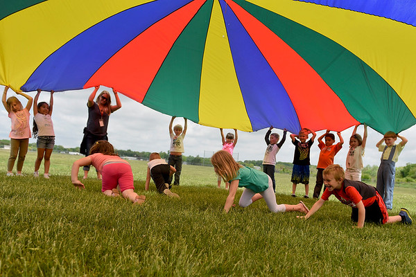 BEN MIKESELL | THE GOSHEN NEWS<br /> Kindergarten students in Jacinda Metz's class crawl underneath a playground parachute during Field Day Tuesday at Benton Elementary School.