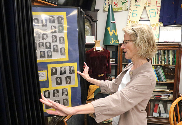 GEOFF LESAR | THE GOSHEN NEWS<br /> <br /> Syracuse-Wawasee Historical Museum Board Member Mary Hursch flips through photos of former local high school students at the museum Wednesday afternoon. Hursch said the photos are one of the more popular sections of the museum.