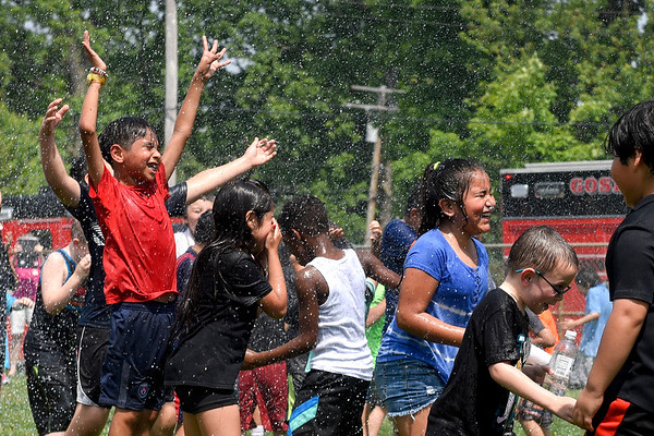 BEN MIKESELL | THE GOSHEN NEWS<br /> Students at Chamberlain Elementary School run through the playground during Field Day Tuesday while being sprayed by Goshen fire fighters. Chamberlain was without air conditioning all day, so Principal Kim Branham said she called Goshen Fire Department to help rescue students from the heat.
