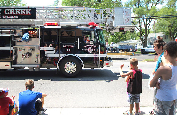 JULIE CROTHERS BEER | THE GOSHEN NEWS<br /> Parade attendees wave to a family inside a Turkey Creek Fire Department truck during the Memorial Day parade Monday in Syracuse.