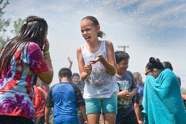 "BEN MIKESELL | THE GOSHEN NEWS<br /> Chamberlain Elementary School fifth-grade student Annika Schrock laughs with classmates while being sprayed by Goshen fire fighters during Field Day Tuesday at Chamberlain. The school was without air conditioning, so Principal Kim Branham called Goshen Fire Department to help rescue the students from the heat. ""Our job encompasses a lot of different things,"" Lt. Courtney Snyder said. ""This is a public service."""