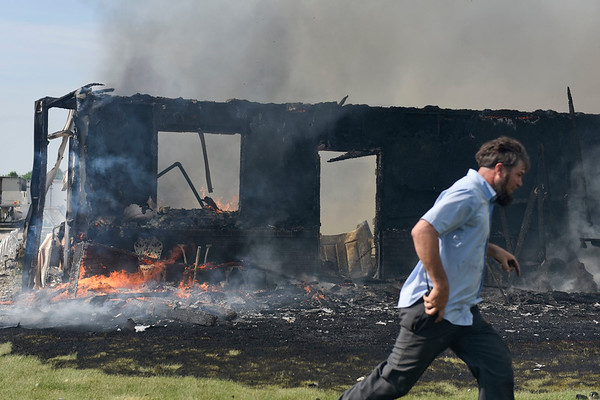 BEN MIKESELL | THE GOSHEN NEWS<br /> A man runs past the burning house Tuesday morning at 11230 C.R. 34 while helping fire fighters on the scene.