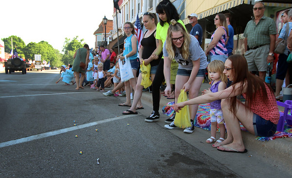 JULIE CROTHERS BEER | THE GOSHEN NEWS<br /> Assisted by her cousin Chloe Leemon, and mom Kyra Davis, nearly two-year-old Zoey Davis of Milford collects candy Monday during the Memorial Day parade in Milford.
