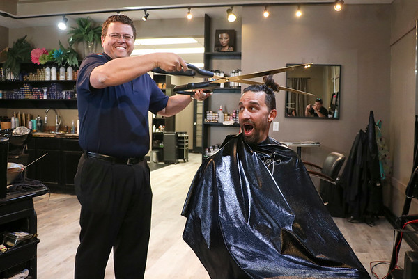LEANDRA BEABOUT | THE GOSHEN NEWS<br /> Nick Kieffer, left, president of the Goshen Chamber of Commerce, holds up a giant pair of scissors to cut off Mayor Jeremy Stutsman's man bun.