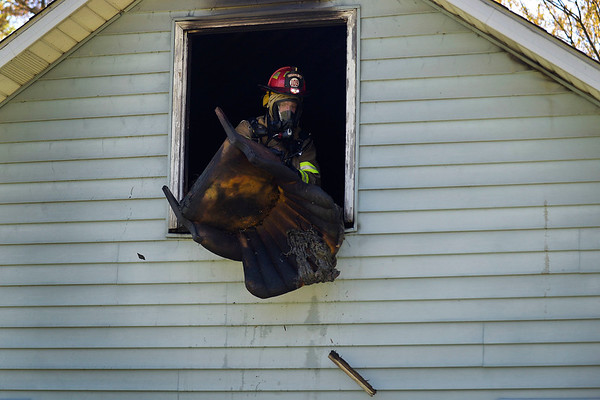 BEN MIKESELL | THE GOSHEN NEWS<br /> A Harrison Township firefighter tosses a burnt chair out of a house at 22285 C.R. 38 Monday. Resident Kathy Wesson called 911 after noticing an abnormal amount of smoke coming from the chimney. Kathy and her daughter Ashley evacuated the house safely with their pets. Harrison, Elkhart Township, Foraker and Wakarusa Fire Departments all responded to the scene.