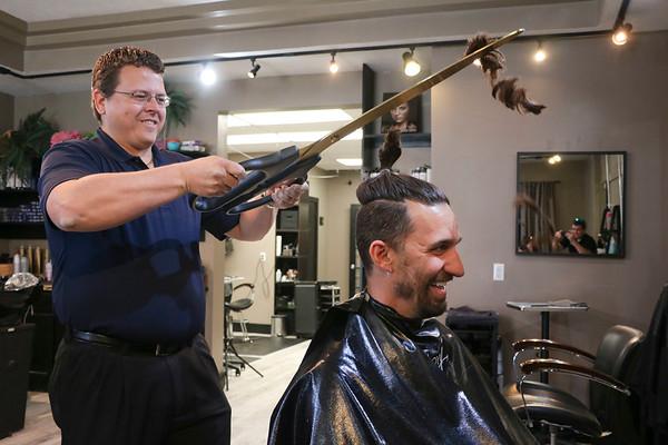 LEANDRA BEABOUT | THE GOSHEN NEWS<br /> Nick Kieffer, left, lops off Mayor Jeremy Stutsman's man bun.