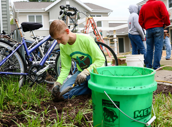 LEANDRA BEABOUT | THE GOSHEN NEWS<br /> Goshen resident Jonah Hochstetler, 17, weeds flower beds around West Plains Apartments for Lacasa's annual Help-A-House day.