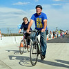 BEN MIKESELL | THE GOSHEN NEWS<br /> Millard Graber, Goshen, rides his bike with his wife Sheila during the public bridge walk Wednesday along the U.S. 33 North Connector route in Goshen. For one hour, the community was allowed to tour the new road before it opens next week.
