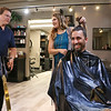 LEANDRA BEABOUT | THE GOSHEN NEWS<br /> Nick Kieffer, left, president of the Goshen Chamber of Commerce, asks stylist Julia Herschberger if he can cut off Mayor Jeremy Stutsman's man bun with a giant pair of scissors.