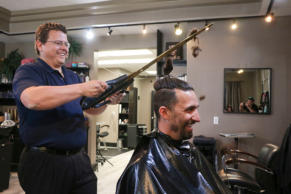 LEANDRA BEABOUT | THE GOSHEN NEWS<br /> Nick Kieffer, left, lops off Mayor Jeremy Stutsman's man bun.