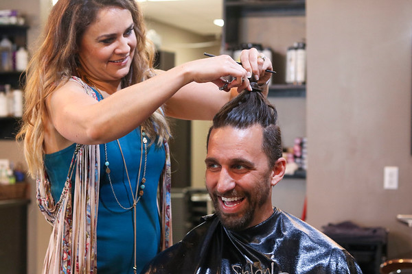 LEANDRA BEABOUT | THE GOSHEN NEWS<br /> Salon owner and stylist Julia Herschberger completed Mayor Jeremy Stutsman's haircut after Nick Kieffer, president of the Goshen Chamber of Commerce, cut off Stutsman's signature man bun.