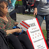 "GEOFF LESAR | THE GOSHEN NEWS<br /> <br /> A woman offers ""impeachmints"" Thursday evening ahead of President Donald Trump's arrival in Elkhart."