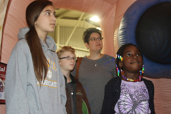 AIMEE AMBROSE | THE GOSHEN NEWS <br /> (from left) Lily Thieszen, 12; Toby Thieszen, 10; Angie Thieszen and Nora Thieszen, 7, all of Millersburg listen to Dr. Sonam Desai of Goshen Health (off frame) as she gives a tour of the Mega Heart during an event hosted by Goshen Health at the Elkhart County Fairgrounds Saturday.