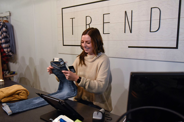 BEN MIKESELL   THE GOSHEN NEWS<br /> Keirsten Miller, co-owner of Trend Clothing, folds up jeans during the opening day of the new store in Linway Plaza in Goshen.