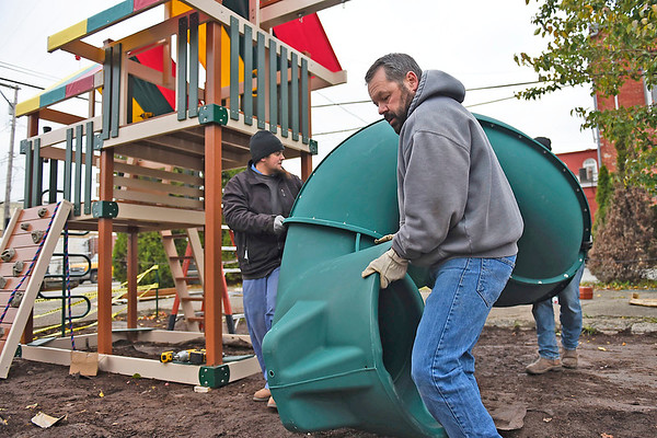 BEN MIKESELL | THE GOSHEN NEWS<br /> Tom Hart, father of Boy Scout Wyatt Hart, helps carry a slide for the new playground being built Tuesday afternoon at Life Spring Community Church in Goshen. His son, a senior at Fairfield Jr.-Sr. High School, raised the funds to build the new playground, which is part of his Eagle Scout project. Wyatt and his troop from New Paris will be on site Saturday to put the finishing touches on the project.