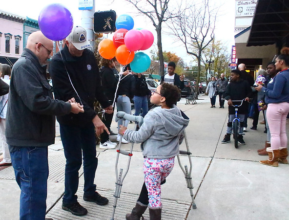 SHEILA SELMAN | THE GOSHEN NEWS<br /> Don Jantzi, Goshen, points to a possible place Kyle Yoder, Goshen, can tie a balloon to the crutches Genna Yoder, 7, is using while they were walking around First Fridays in downtown Goshen Friday night.
