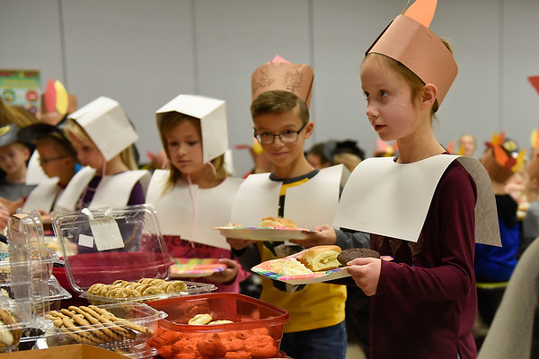 BEN MIKESELL | THE GOSHEN NEWS<br /> First-grader Kandyce Kauffman waits in line to get her food during a Thanksgiving lunch Tuesday afternoon at New Paris Elementary School. Several local schools served special holiday-themed meals Tuesday ahead of Thanksgiving.