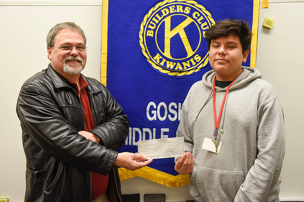 BEN MIKESELL | THE GOSHEN NEWS<br /> Ed Swartley, Executive Director with The Window, left, stands with 8th-grader Jesse Iniguez Thursday at Goshen Middle School. Through a school-wide penny war last week, GMS students raised $1535.20, which was donated to The Window. Iniguez, a member of the Builders Club, stayed after school every day this week to count up the pennies, nickels and dollars donated through the week.