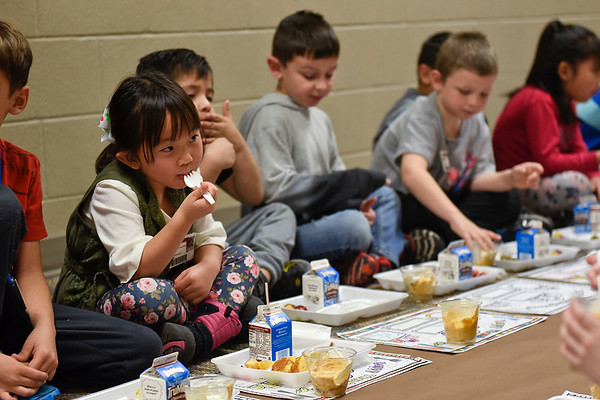 BEN MIKESELL | THE GOSHEN NEWS<br /> First-grader Katelyn Wiking enjoys a Thanksgiving feast with her classmates Tuesday in the first-grade hallway at Waterford Elementary School.