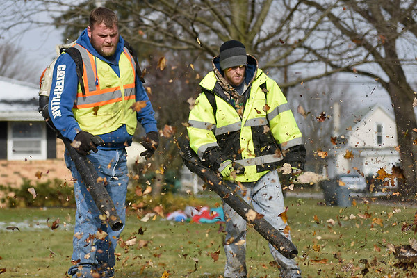 BEN MIKESELL | THE GOSHEN NEWS<br /> Goshen Street Department workers Justin German, left, and Justin Gaines, right, blow leaves onto Hickory Street during leaf pickup Monday in Goshen.