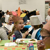 BEN MIKESELL | THE GOSHEN NEWS<br /> First-grader Kyla Schmidt laughs with her classmates while enjoying a Thanksgiving meal Tuesday at New Paris Elementary School.