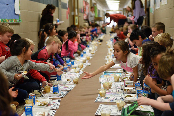 BEN MIKESELL | THE GOSHEN NEWS<br /> First-grader Rubi Briano, right, reaches across the table while enjoying a Thanksgiving feast with her classmates Tuesday in the first-grade hallway at Waterford Elementary School.