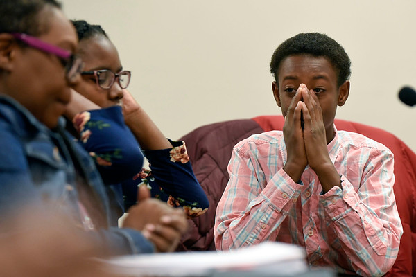BEN MIKESELL | THE GOSHEN NEWS<br /> Lindani Logan, 12, wipes tears from his eyes before he is officially adopted by Rita McKinney, of Elkhart, Friday morning at the Elkhart County Juvenile Court in Elkhart. Logan began living with McKinney and her daughter August Shorter when he was seven.