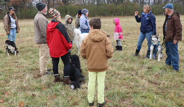 JOHN KLINE | THE GOSHEN NEWS<br /> Belva Sutton Dreer, co-founder of Heartland Mushers Association, second from right, and Heartland member Keith Miller, right, speak to attendees of a Mushing 101 class held at River Preserve County Park Saturday afternoon.