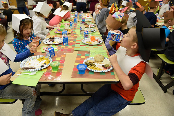 BEN MIKESELL | THE GOSHEN NEWS<br /> First-grader Jacob Bechtel, dressed as a pilgrim, chugs his chocolate milk during a Thanksgiving meal Tuesday at New Paris Elementary School.