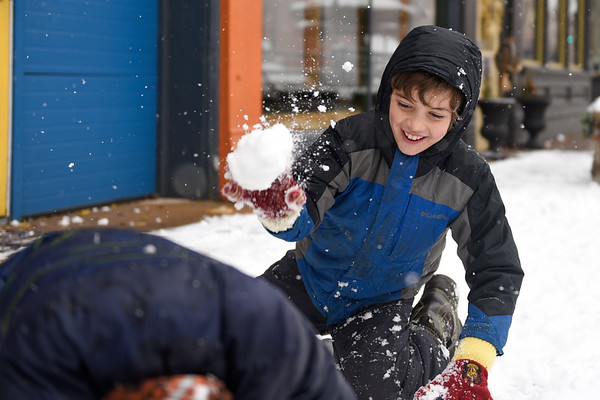 BEN MIKESELL | THE GOSHEN NEWS<br /> Makai Hochstetler, 10, throws a snowball at his step-brother Malachi Paul, 9, while making a snowman on the sidewalk outside Ignition Music Garage in downtown Goshen. The brothers, who attend Bethany Christian Schools, had the day off due to the snow. Goshen received about 1.3 inches of snow throughout Thursday morning, but the rest of the week should be relatively calm, meteorologist Geoffrey Heidelberger at the National Weather Service said.