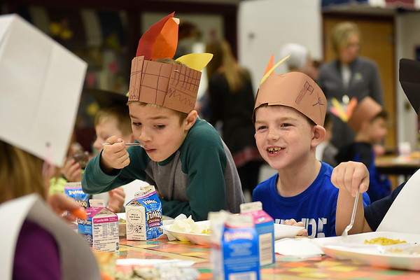 BEN MIKESELL | THE GOSHEN NEWS<br /> First-graders Devin Raysin, left, and Damien Risner, right, enjoy their Thanksgiving meals Tuesday with their classmates at New Paris Elementary School.