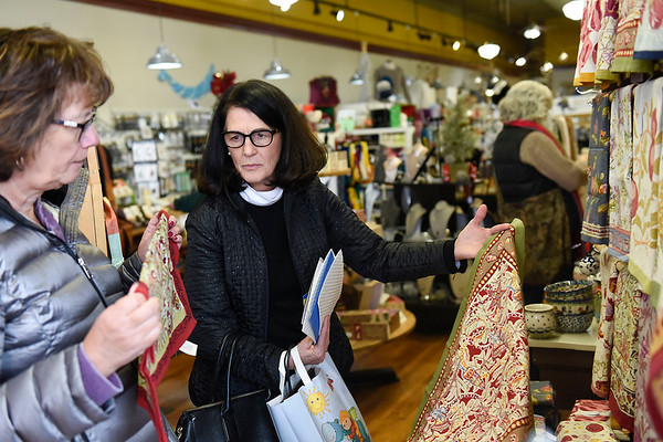 BEN MIKESELL | THE GOSHEN NEWS<br /> Gail Nichols, of Goshen, holds up a tea towel while shopping with Patrice Traxler, of Goshen, Tuesday afternoon at Rêverie Yarn, Decor & Gifts in Goshen.