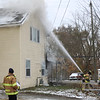 AIMEE AMBROSE | THE GOSHEN NEWS <br /> Goshen firefighters spray a hot spot after responding to a fire that heavily damaged a house at 102 Olive St. Friday afternoon.