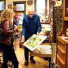 SHEILA SELMAN | THE GOSHEN NEWS<br /> Found co-owner Keith Graber Miller shows customer Glenda Koshmider, Goshen, a print during Shop Small Business Saturday in downtown Goshen.