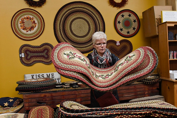 BEN MIKESELL | THE GOSHEN NEWS<br /> Melody Norton, of Orland, flips through mats while shopping for Wana Night Out at Truly Yours inside Davis Mercantile in Shipshewana. In tune with the city-wide shopping event, Truly Yours offered 25 percent off purchases for the whole day.