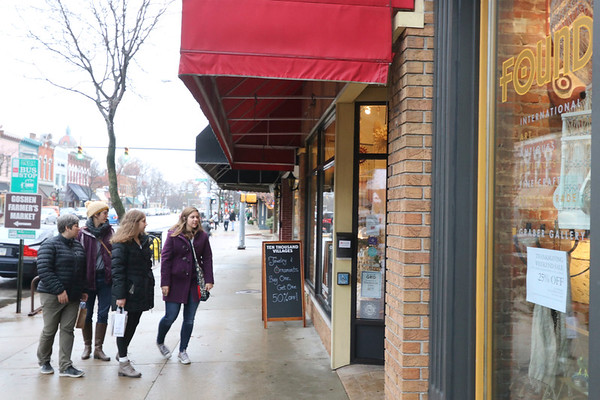 AIMEE AMBROSE | THE GOSHEN NEWS <br /> A group heads into Ten Thousand Villages on Main Street while walking in downtown Goshen during the Small Business Saturday event on Saturday.